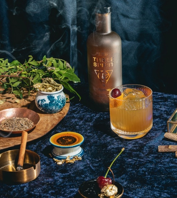 A Nightcap Old Fashioned cocktail surrounded by the plant ingredients, inlcuding cherry